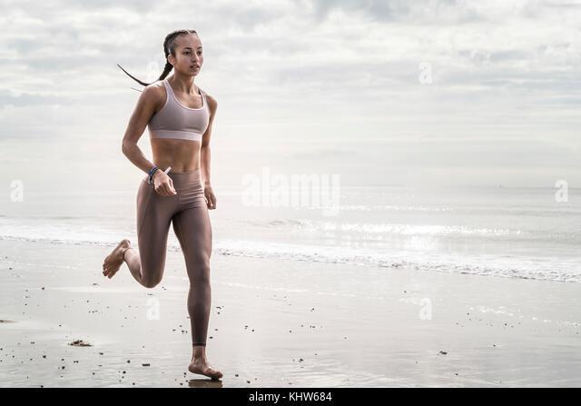 Junge Frau Strand entlang läuft Stockbild