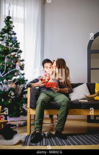 Man-Eröffnung ein Geschenk, während ihre Freundin sitzen in ihrer Nähe auf der Couch Stockbild