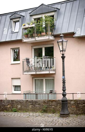Nostalgische Laterne vor einem Wohnhaus mit kleinen Balkonen, Stockbild