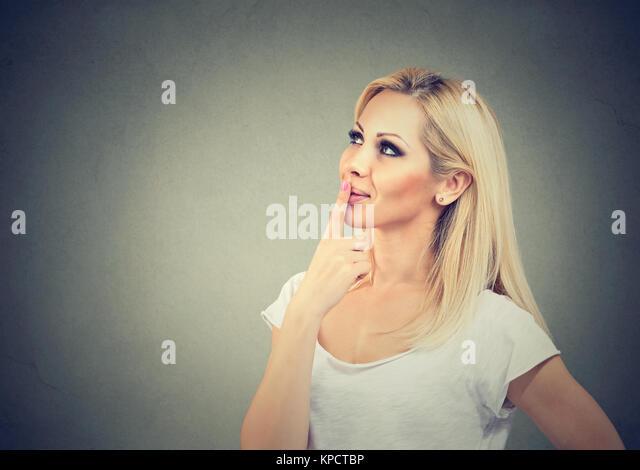 Junge blonde berühren Lippen beim Gedanken an etwas glücklich und weg schauen auf grauem Hintergrund Stockbild