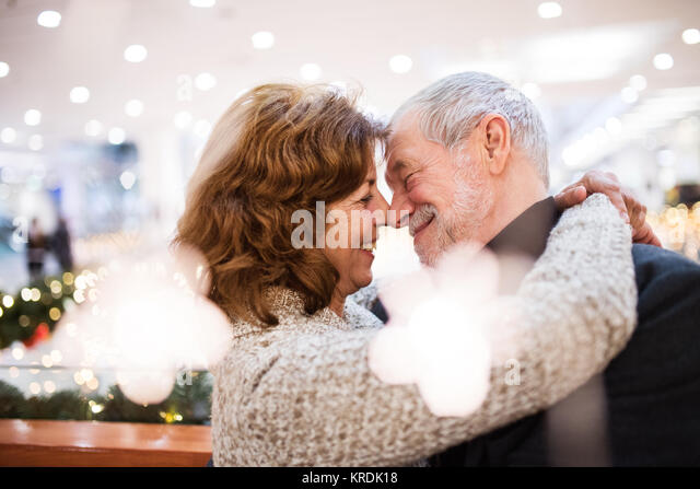 Senior Paar, Christmas shopping, umarmen. Stockbild