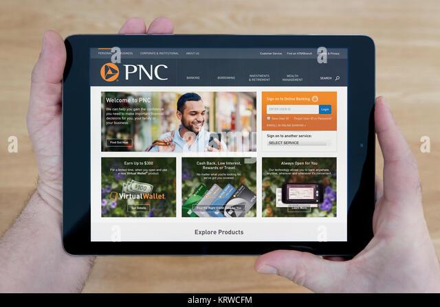 Ein Mann schaut auf die PNC Financial Services Website auf seinem iPad tablet device, Schuß gegen einen hölzernen Stockbild