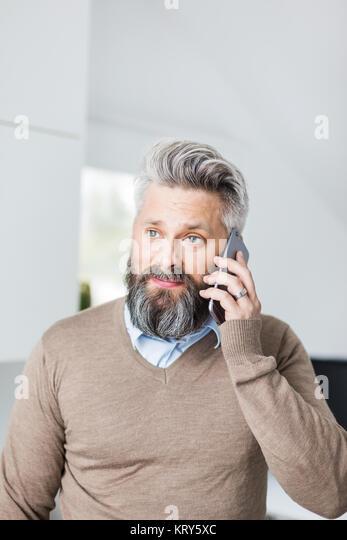 Ein Mann in einer braunen Pullover im Gespräch mit einem Mobiltelefon Stockbild