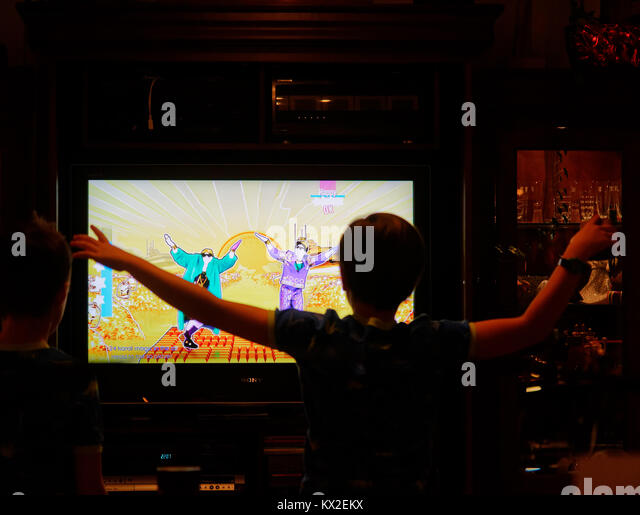 Ein Junge (9 Jahre alten) tanzen vor dem Fernsehgerät mit dem PlayStation 4-Spiel nur Tanz Stockbild