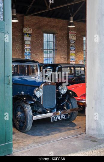 Oldtimer, darunter ein Austin 1934 in einer Garage im Bicester Heritage Center. Bicester, Oxfordshire, England. Stockbild