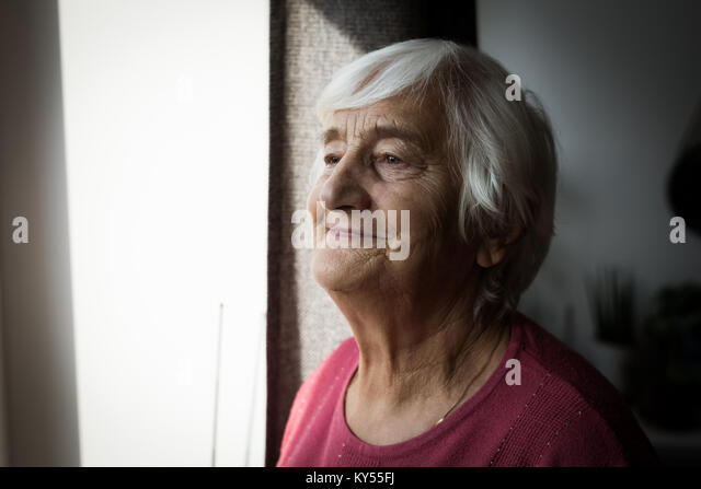 Ältere Frau stehen in der Nähe von Fenster Stockbild