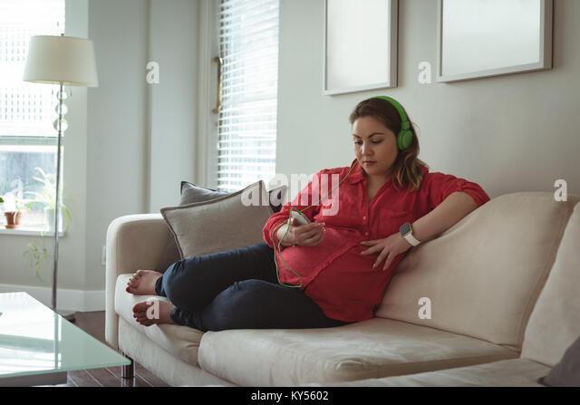 Junge schwangere Frau sitzt auf einem Sofa Liste Musik auf Ihrem Mobiltelefon Stockbild