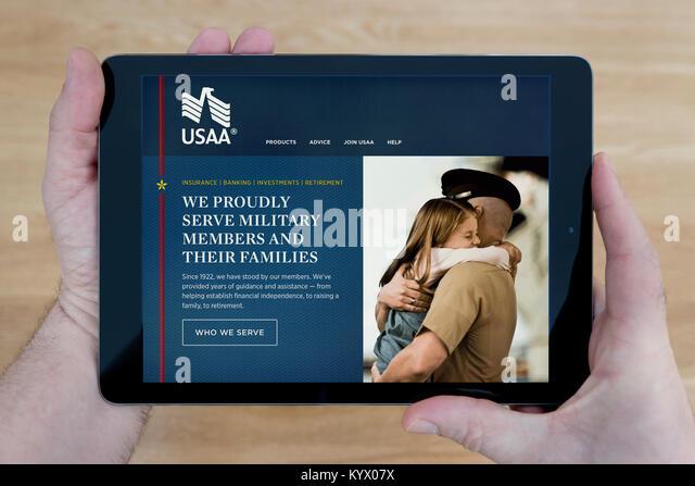 Ein Mann schaut auf die United Services Automobile Association (Usaa) Website auf seinem iPad Tablet, mit einem Stockbild