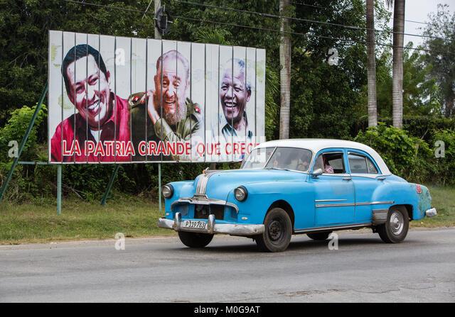 Classic American Auto fahrend hinter Reklametafeln von Hugo Chavez, Fidel Castro und Nelson Mandella in Cienfuegos, Stockbild