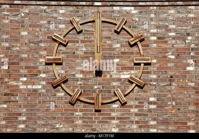 Goldene Uhr auf braun Mauer, Bremen, Deutschland, Europa ich Goldene Uhr in bräunlicher Backsteinwand, Bremen, Stockbild