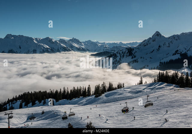 Schnee auf den Höhen der Berge und Nebel das Tal hinunter Stockbild