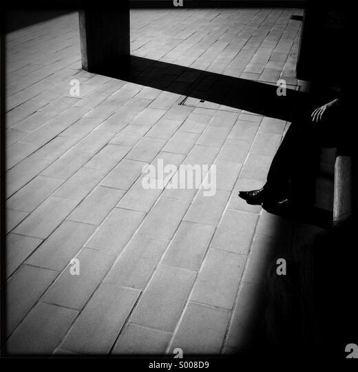 Mann sitzt auf einer Bank durch Schatten verdeckt. Stockbild