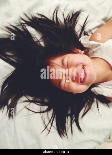 Junges Mädchen Bett lächelnd Handauflegen Stockbild