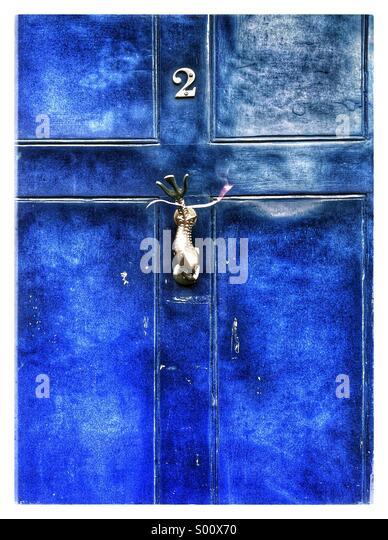 Eine helle blaue farbige Tür mit einem Fisch geformt Klopfer. Stockbild