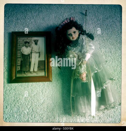 Ein Familienporträt und eine Puppe schmücken ein Haus in Teotitlan del Valle, Oaxaca, Mexiko Stockbild