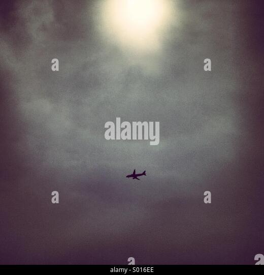 Flugzeug bei bewölktem Himmel die Sonne versteckt Stockbild