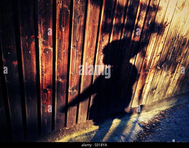 Schatten des 3 jährigen Jungen auf Holzwand. Stockbild