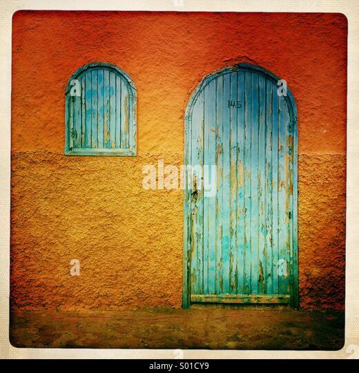 Blaue Tür und Fenster gegen orange Wand in Marokko. Stockbild
