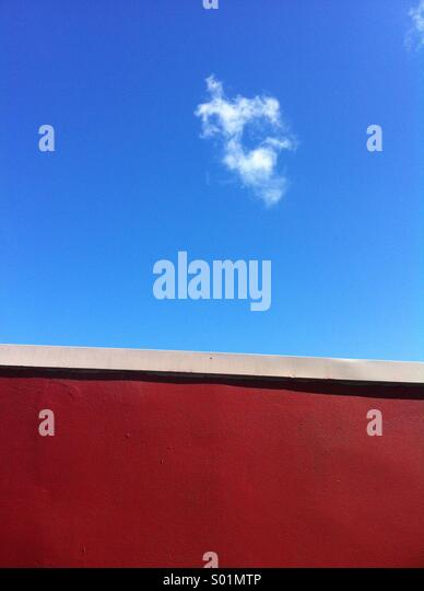 Rote Wand und blauer Himmel mit der cloud Stockbild