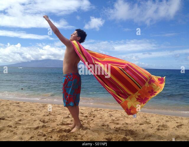 Junge, im Alter von 12 spielen mit Strandtuch, Hawaii Stockbild