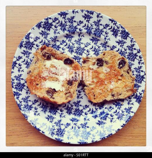 Butter schmelzen auf beiden Hälften der ein Hot Cross Bun, auf einem Vintage blaue und weiße Blumen Teller. Stockbild