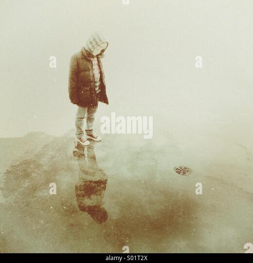 Kleiner Junge stand in einer Pfütze sein Spiegelbild zu betrachten, bevor das Wasser des nahe gelegenen Bach Stockbild