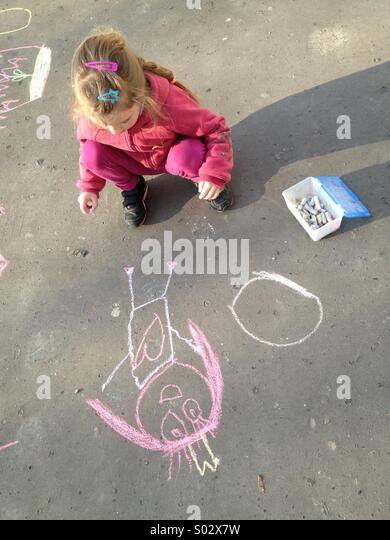 Kleines Mädchen zeichnen mit Kreide auf asphalt Stockbild