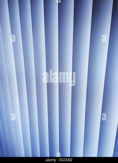 Eine Vertikaljalousie mit geschlossenen Lamellen in der Innenansicht Wohnung mit blauem Licht. Stockbild