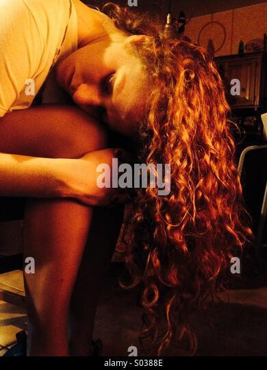 Eine rothaarige Mädchen trocknet Haare in der Nähe des Ofens Stockbild