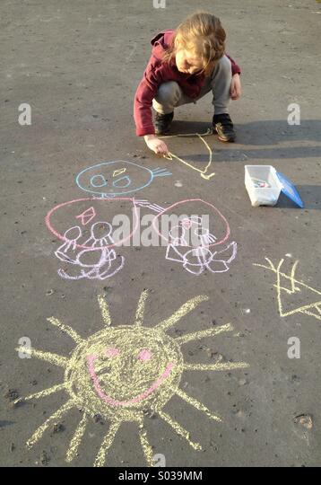 Kleines Mädchen mit Kreide zeichnen Stockbild