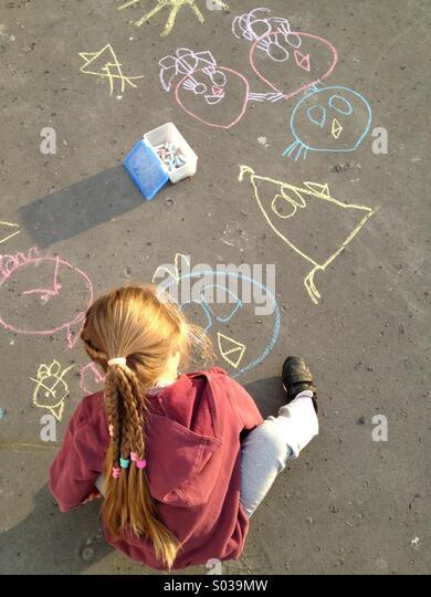 Kind zeichnen mit Kreide auf asphalt Stockbild
