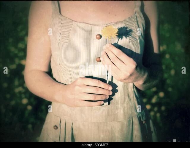 Frau trägt ein weißes Kleid, eine Löwenzahn Blume Stockbild