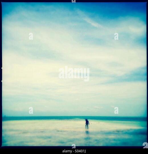 Kleines Mädchen erkunden den Strand Stockbild