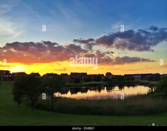 Häuser mit Blick auf See bei Sonnenuntergang, Hampton Vale, Peterborough, UK Stockbild