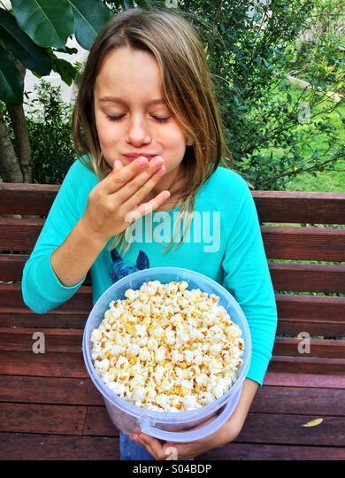 Junges Mädchen essen popcorn Stockbild