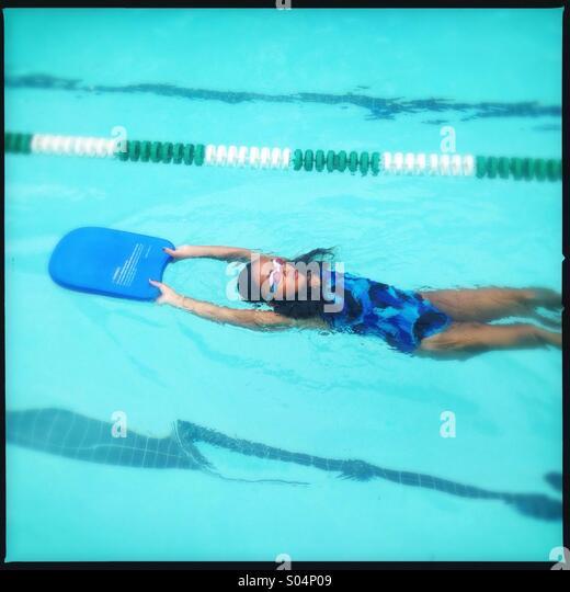 Kleines Mädchen lernen, wie man auf dem Rücken schwimmen Stockbild