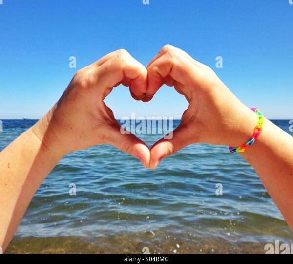 Händen Liebesherz gegen das Meer Stockbild