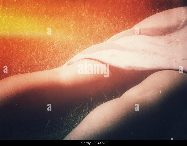 Sonnenbrand-Konzept. Beine und Rock einer Frau auf dem Rasen Sonnen Stockbild