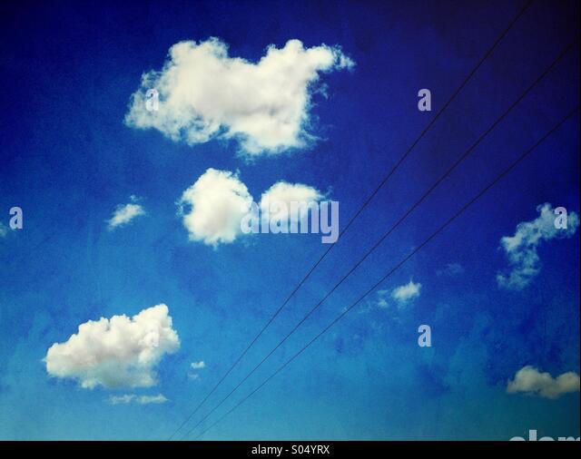 Pylon Drähte und weiße Wolken gegen blauen Himmel Stockbild