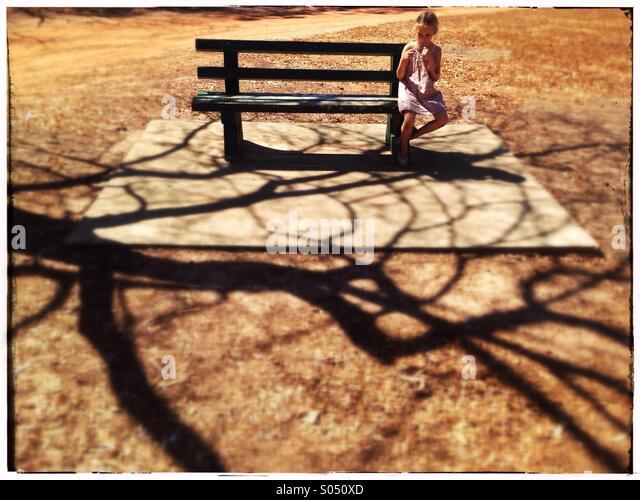 Kleines Mädchen auf einer Parkbank. Stockbild