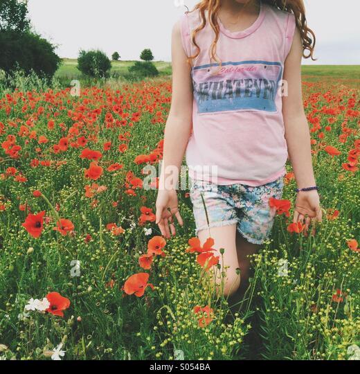 Mädchen zu Fuß durch ein Mohnfeld Stockbild