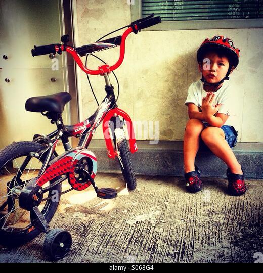Kleine asiatische Junge sitzt neben seinem kleinen BMX-Rad Stockbild