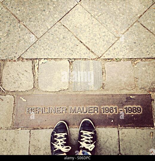 Berliner Mauer Gedenksteine in Pflaster mit Füßen Stockbild