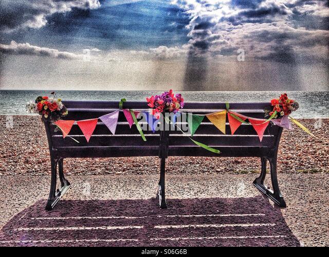 Bank am Meer mit Blumen und Girlanden geschmückt Stockbild