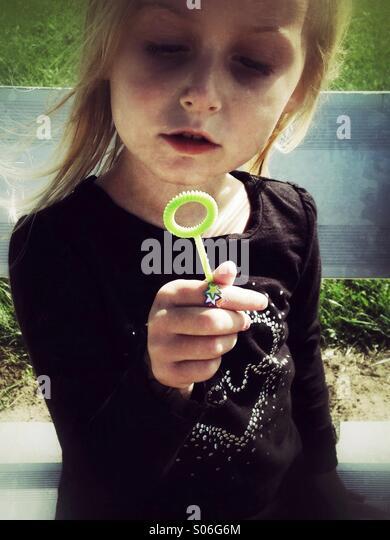 Ein Kind und ihre Blase Zauberstab machen. Stockbild