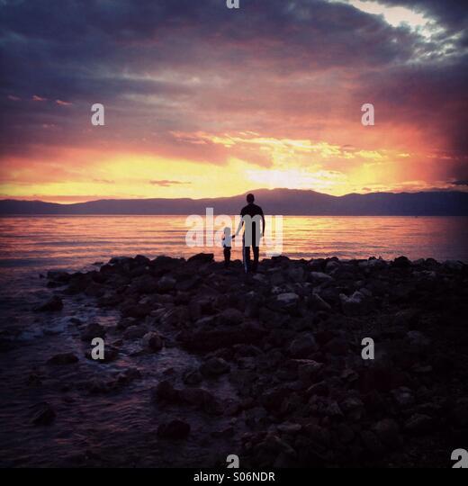 Vater und Sohn am Meer bei Sonnenuntergang Stockbild