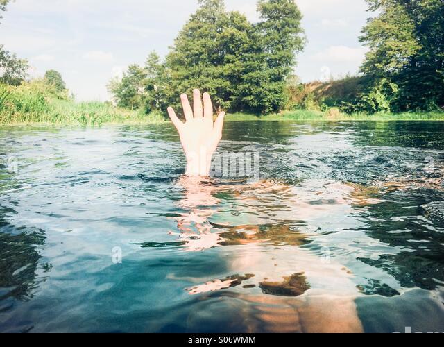 Junge in einem reinen Fluss hält seine Hand über dem Wasser untergetaucht Stockbild