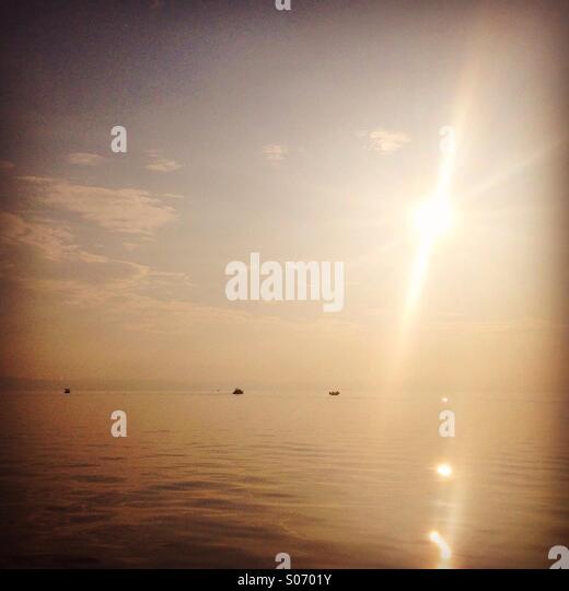 Kleine Boote bei ruhiger See mit Sonne Reflexion Stockbild