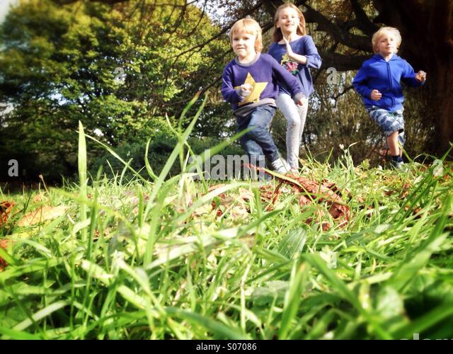 Kinder laufen über ein Feld Stockbild