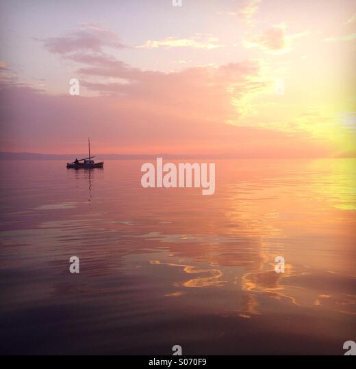 Kleines Boot auf hoher See in farbenprächtigen Sonnenuntergang Stockbild
